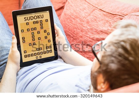 technology lifestyle concept: hipster on the sofa gaming sudoku application - stock photo