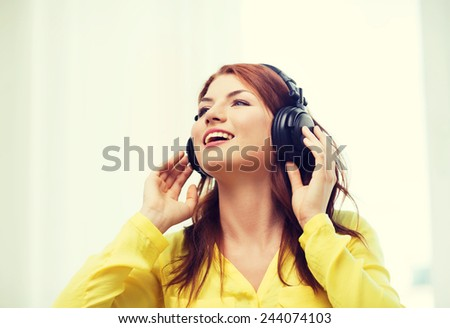 technology, music and happiness concept - smiling young girl in headphones at home - stock photo