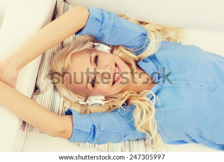 technology, music and happiness concept - smiling young girl lying on sofa in headphones at home - stock photo