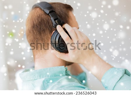technology, music, leisure and people concept - close up of man in headphones at home from back - stock photo