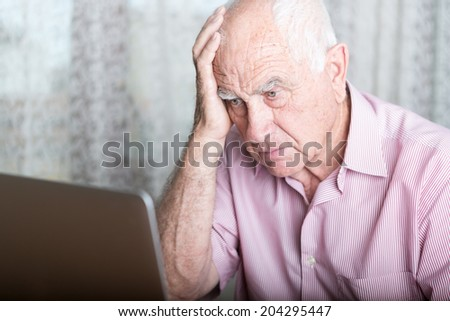 technology, oldness and lifestyle concept - old man in working with laptop computer at home concerned - stock photo