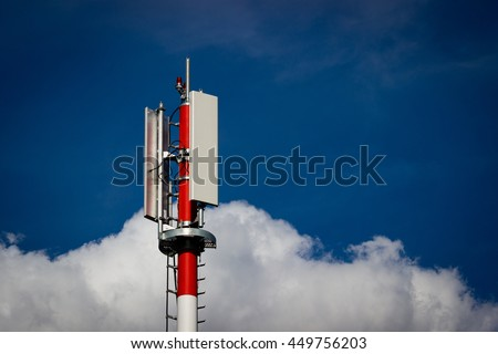Technology on the top of the GSM tower (antenna pillar, transmitter), red and white striped pole, blue sky, white cloud - stock photo
