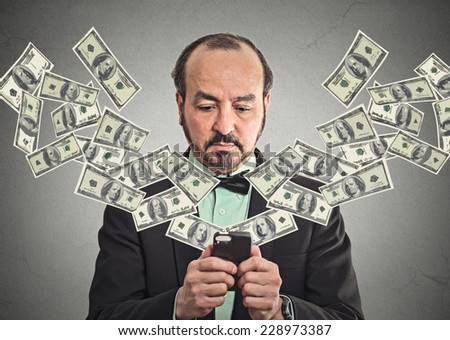 Technology, online banking, money transfer, e-commerce concept. Middle aged businessman in suit and bow tie using smartphone dollar bills flying from screen isolated grey wall office background. - stock photo