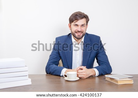 Technology, people and business concept - handsome man with beard and brown hair and blue suit and tablet and some books looking at camera with smile in the office.  Isolated on white background.   - stock photo