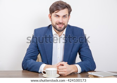 Technology, people and business concept - handsome man with beard and brown hair and blue suit and tablet pc computer and some books looking at camera with smile. Isolated on white background.   - stock photo