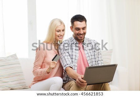 technology, people, e-money and commerce concept - smiling happy couple with laptop computer and credit or bank card shopping online at home - stock photo