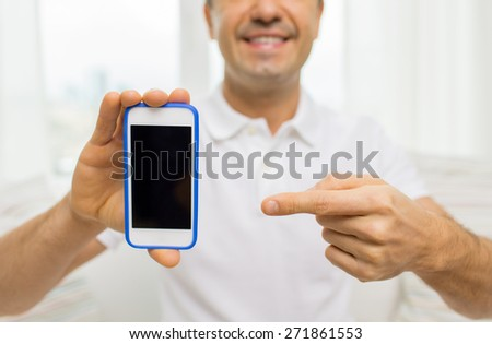 technology, people, lifestyle and communication concept - close up of happy man showing smartphone black blank screen at home - stock photo