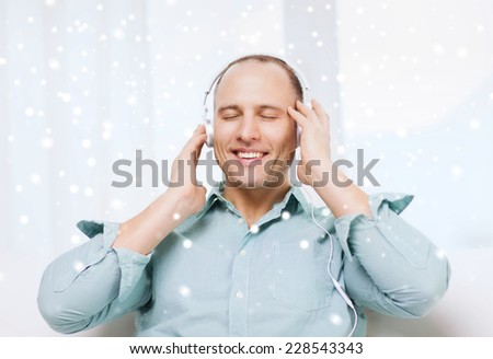 technology, people, winter and leisure concept - smiling man in headphones listening to music at home - stock photo