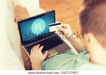technology, shopping, banking, home and lifestyle concept - close up of man with laptop computer and credit card at home - stock photo