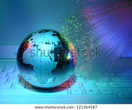 technology steel earth on laptop keyboard against fiber optic background - stock photo