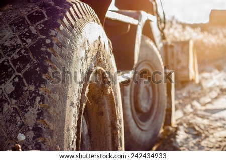 Technology, transportation, construction. Close-up wheel excavator. Frozen ground. Lateral modal sun. - stock photo