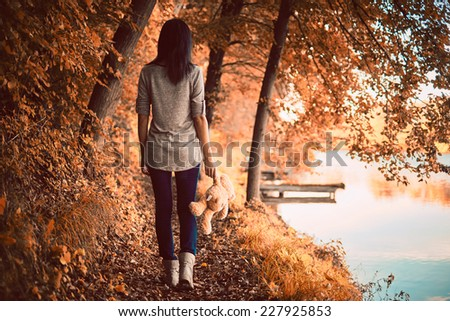 Teddy bear and girl in the woods - stock photo