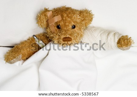 Teddy bear as a patient in hospital's bed with medical thermometer. - stock photo