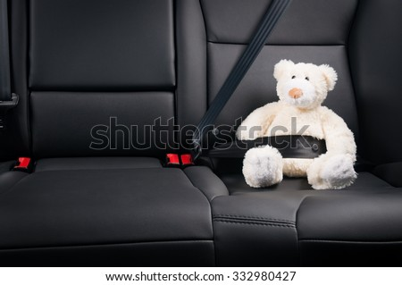 Teddy bear fastened in the back seat of a car, safety on the road - stock photo