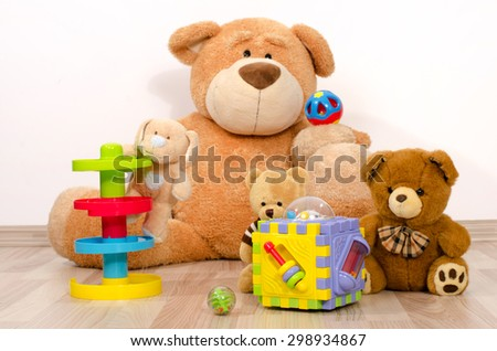 Teddy bear having fun. Many bear toys playing, one big bear watching his little bears playing with balls and boxes - stock photo