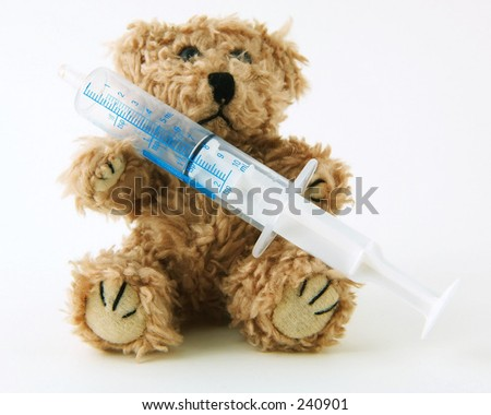 Teddy bear holding a syringe used to measure medication on a white background - stock photo