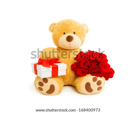 Teddy bear holding gift box and bouquet of red roses, valentines day. Studio shot, over white background with copy space. - stock photo