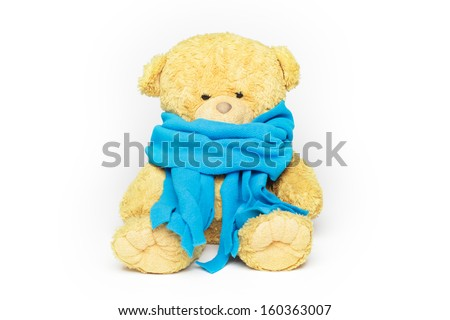 Teddy bear in a blue scarf. The bear looks sick and sad. Isolated on white. - stock photo