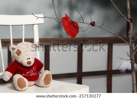 Teddy bear in Valentine's day on back of chair - stock photo