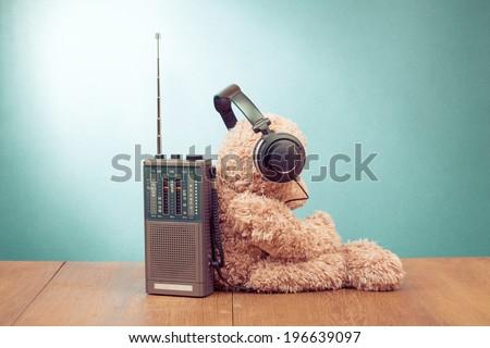 Teddy Bear listen headphones, retro radio front mint green background - stock photo