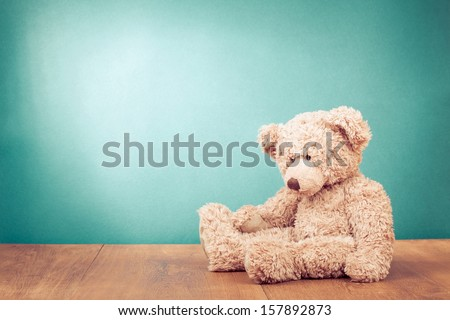 Teddy Bear toy alone on wood in front mint green background - stock photo