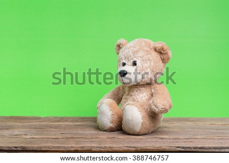 Teddy Bear toy alone on wood with green background. - stock photo