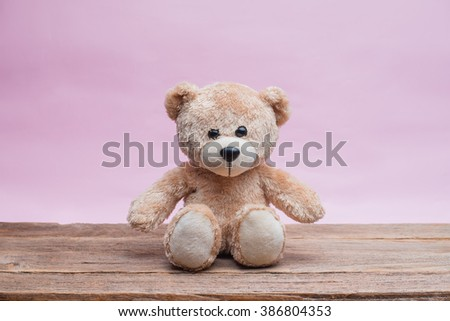 Teddy Bear toy alone on wood with light pink background. - stock photo