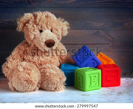 Teddy Bear toy and cubes on wood background - stock photo