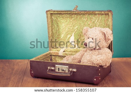 Teddy Bear toy sitting in old retro suitcase - stock photo