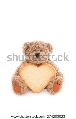 Teddy bear with a heart-shaped rusk, isolated on white - stock photo