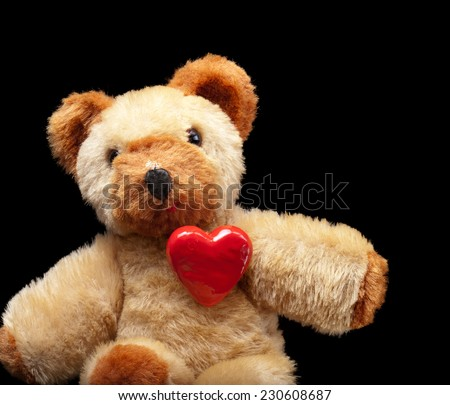 Teddy bear with a read heart on his chest on a black background. - stock photo