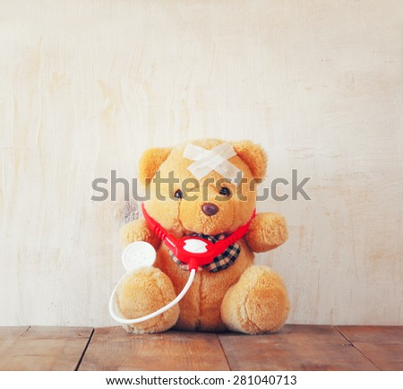 Teddy Bear with Bandage  and  stethoscope over wooden background - stock photo