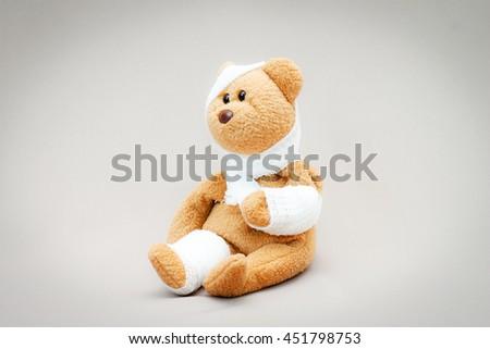 Teddy bear with bandage on gray background. - stock photo