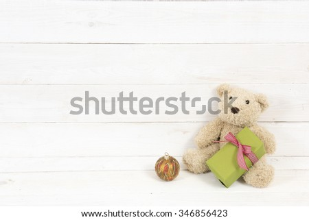 teddy bear with gift on white wooden background - stock photo