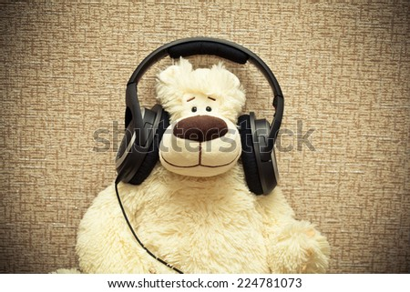 Teddy bear with headphones. Lover of music. Photo tinted in yellow  - stock photo