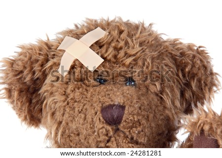 Teddy bear with plaster on the head on a over white background - stock photo