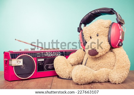Teddy Bear with red headphones and retro radio cassette recorder from 80s - stock photo