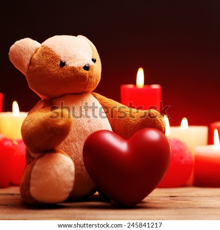 Teddy Bear with red heart and candles on dark background - stock photo