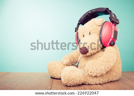 Teddy Bear with red retro headphones front mint green background - stock photo