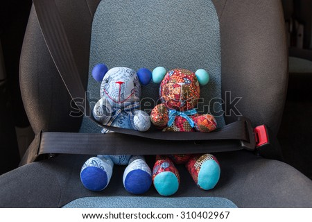 Teddy bears with seat belt fastened - stock photo