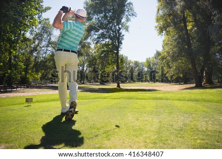 Teeing of with iron, golf ball visible in the sky - stock photo