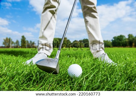 Teeing off. Close-up of male golfer teeing off while standing on golf course - stock photo