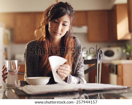 teen asian girl studying in kitchen - stock photo