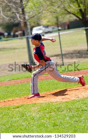 Teen baseball pitcher in the middle of throw - stock photo