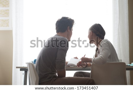 Teen boy and girl sitting together and studying at home - stock photo