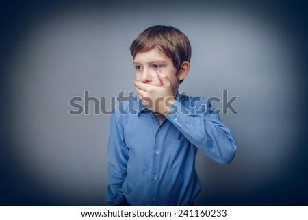 Teen boy European appearance brown hair hand closed mouth feels fear cross process - stock photo