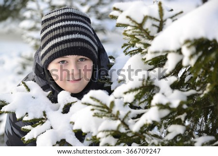 Teen boy looks out from behind trees in the winter forest - stock photo