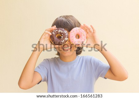 teen boy making fun with multicolored donuts - stock photo