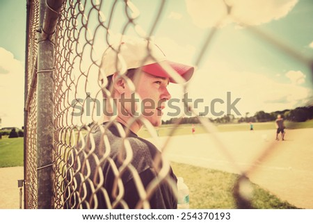 Teen boy on sidelines at baseball practice. Instagram effect. - stock photo