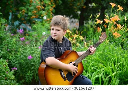 Teen boy playing guitar outdoor in summer - stock photo